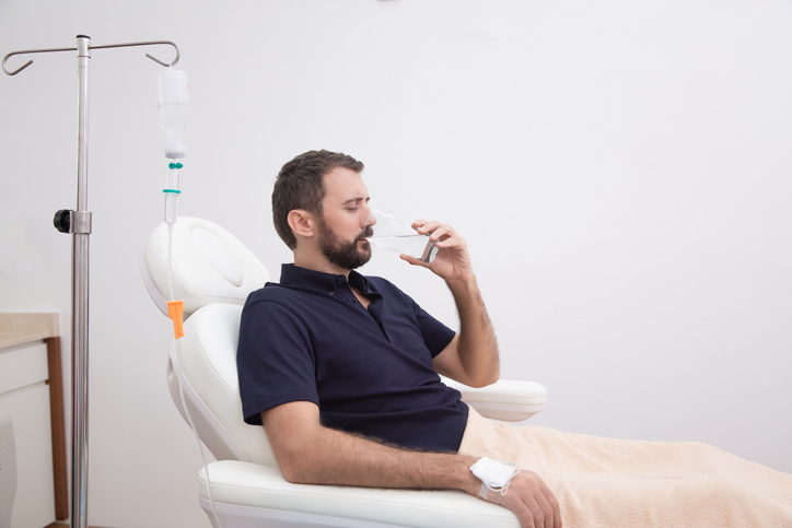 patient receiving resilience iv vitamin therapy and drinking a glass of water